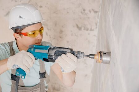 Builder man cutting electrical chase in concrete wall with hammer drill diamond crown