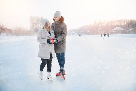 Surprise romantic for Valentine Day or Christmas. Man giving gift box girlfriend winter on ice rink, background snow sunset