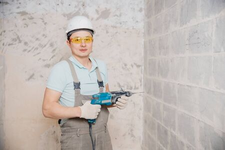 Portrait man builder repairer in protective glasses, hard hat, overalls showing having equipment in arm on grey background home brick
