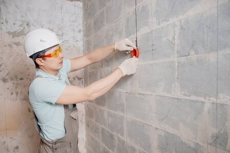Builder worker installs plastic box under electrical outlet in hole wall