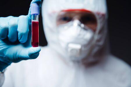 Blood test, medic in white hazmat protective.