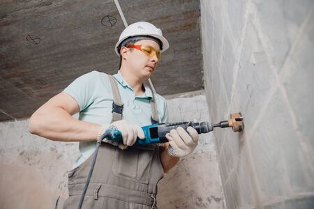 Builder worker pneumatic hammer drills hole in concrete brick wall with diamond crown for electric cable, socket, switch