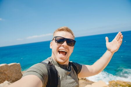 Happy traveler man taking selfie photo in sunglasses on background of bruise sea with backpack. Travel concept Banque d'images