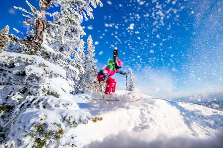 Woman skier jumping in pink skis on background of blue sky and snowy forest in mountains, dust from snow Stock fotó