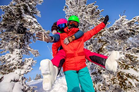 Snowboarder man and woman skier hugging and having fun on background of winter forest and snow. Sunlight in mountains