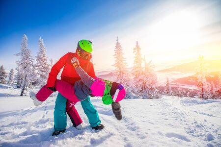 Loving couple woman and man having fun and fooling around in winter forest. Skier and snowboarder on background of blue sky Stock Photo