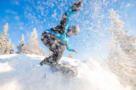 Active man snowboarder riding on slope during sunny day in mountains. Dust snow forest