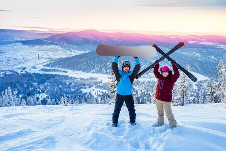 Friends snowboarder and skier standing on mountain top blue sky sunrise. Concept ski resort winter forest.