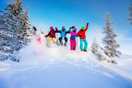 Team of friends skiers and snowboarders are jumping in fresh snow in winter forest. Stock Photo