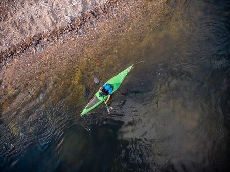 Guy in kayak sails mountain river. Whitewater kayaking, extreme sport rafting. Aerial top view