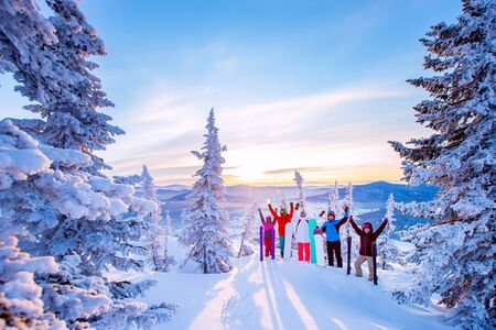 Beautiful winter landscape with forest snow in mountains with team of friends snowboarders and skiers sunrise.