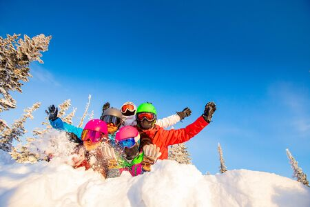 Group of happy friends having fun in winter forest. Snowbarders and skiers group team friendship ski resort.