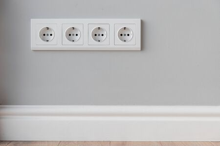 White European sockets on gray concrete wall in loft style, with high polyurethane baseboard