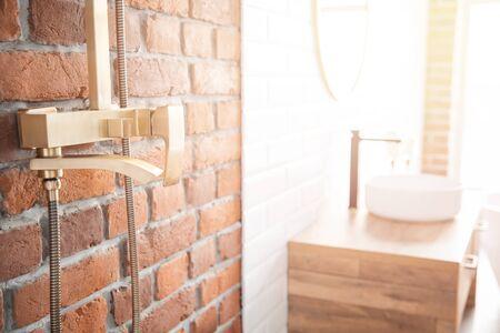 Modern shower system copper color for bathroom in loft style, brick wall. Sunlight window. Zdjęcie Seryjne