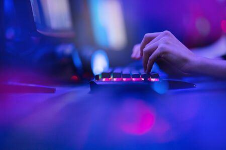 Hacker uses keyboard, shakes buttons with fingers to crack password. Internet security concept, cyber attack. Neon blue color.