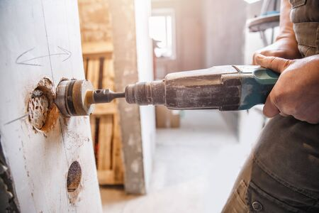 Builder worker pneumatic hammer drills hole in concrete brick wall with diamond crown for electric cable, socket, switch.