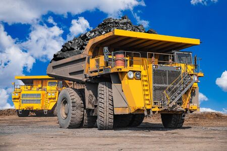 Open pit mine industry, big yellow mining truck for coal anthracite. Foto de archivo