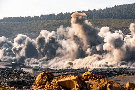 Explosive works on open pit coal mine industry with dust and puffs of smoke.