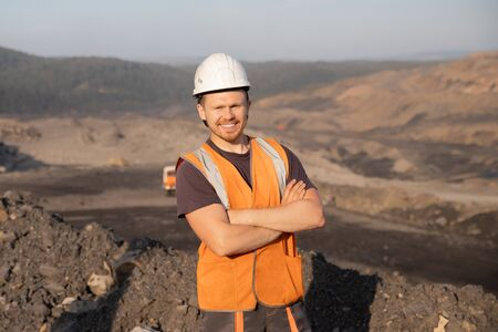 Engineer smiling man in white helmet on background open pit mine industry