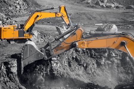 Excavator work loading of coal into Yellow mining truck. Open pit mine industry.