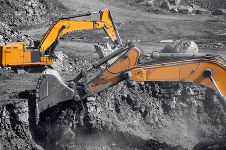 Travaux d'excavatrice chargeant du charbon dans un camion minier jaune. Industrie minière à ciel ouvert.