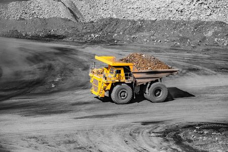 Big yellow mining truck transportation of gold ore. Open pit mine industry.