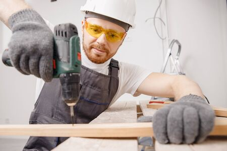 Worker man carpenter screws metal into wooden board with electric screwdriver Stock Photo