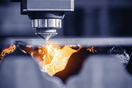 CNC gas cutting metal sheet, sparks fly. Blue steel color, modern industrial technology.