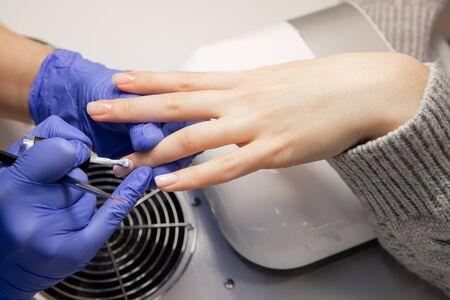 Closeup beautiful hands woman getting nail care manicure in spa salon. Imagens