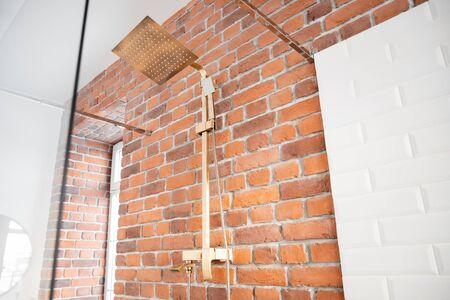 Modern shower system copper color for bathroom in loft style, brick wall. Sunlight window.