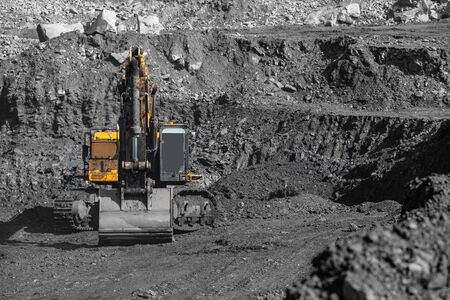 Yellow excavator works and extracts coal from bowels of earth. Open pit mine industry
