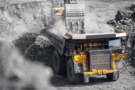 Open pit mine industry. Yellow mining truck for coal move to excavator loads. Stockfoto