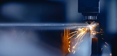 Blue color Laser CNC cut of metal with light spark, technology modern industrial.