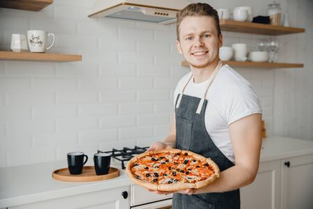 Homemade Italian pizza, handsome young male chef in dark apron holds baking sheet in bright kitchen. Cooking video blog concept