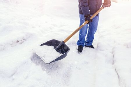 Man worker shovel cleaning snow winter street in front of house after big snowstorm