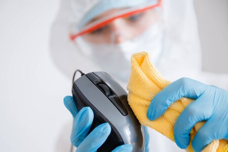 Cleaning service disinfects office Technics from coronavirus and germs, antiseptic processing computer Stock Photo