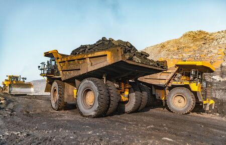 Big yellow mining truck laden anthracite moves open pit coal mine.