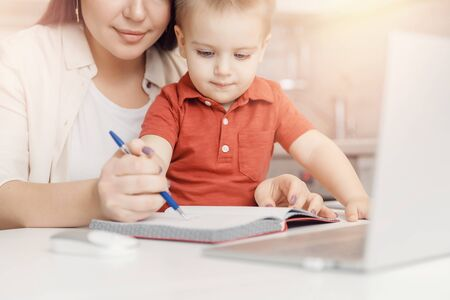 Mother and son are learning to write. Woman teaches kid alphabet Online study