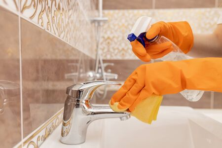 Cleaning tap from limescale in bathroom, disinfecting surface from contamination 写真素材