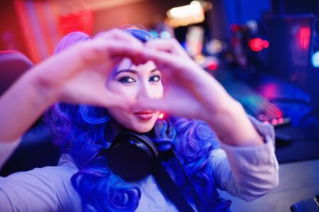 Cosplay young beautiful woman with blue hair welcomes subscribers to stream for video games, neon color 写真素材