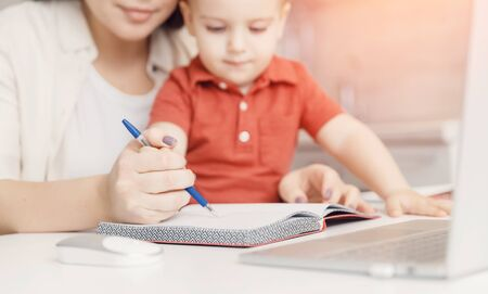 Mother teaching her kid son how to write pen. concept Online learning quarantine