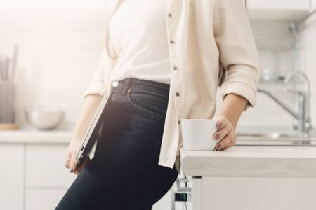Young woman freelancer holds laptop and coffee in kitchen home. Concept work online quarantine