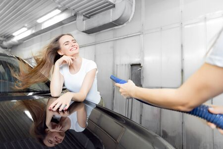 Girl worker uses turbo dryer to remove drops of water. Service car wash express