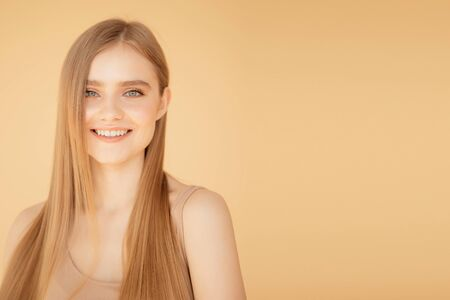 Beauty portrait smiling young woman with blonde hair, isolated over beige background