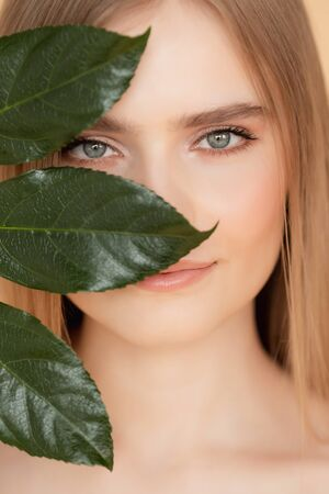 Portrait woman with natural green leaf, blond model girl with clear skin face. Concept Fashion flora beauty