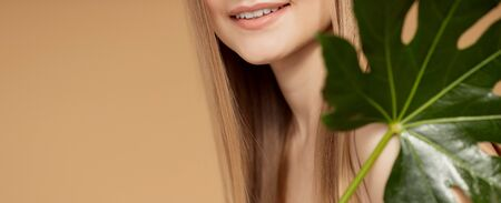 Concept oral care teeth and gums.Portrait woman with natural green leaf, blond model girl with smile