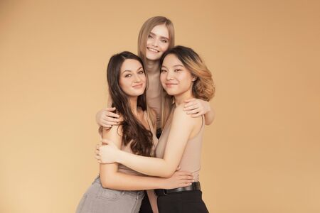 Group multiracial women standing hug and looking camera. Friendship posing together asian, blonde, brunette