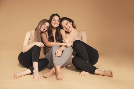 Happy young multicultural Asian women, Caucasian hugging and laughing in studio on beige background. Beauty spa treatment skin care concept