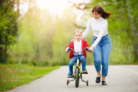 Mom teaches little son to ride bike in park, keep balance, have fun family. Mother day concept 写真素材