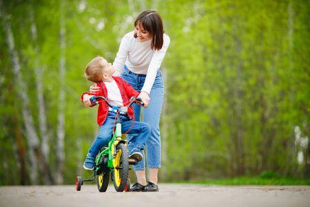 Mom woman teaching his little kid to ride bike